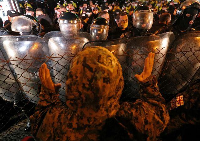 Homem gesticula para policiais em protesto em Tbilisi, na Geórgia