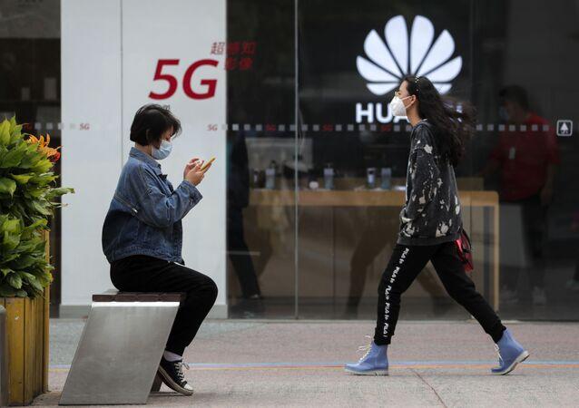 Mulher usando máscara para se proteger do SARS-CoV-2 mexe no smartphone perto de loja da Huawei promovedora da rede 5G em Pequim, China, 11 de outubro de 2020