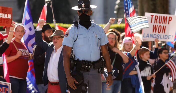 Policial acompanha manifestação de apoiadores de Trump em Atlanta, Geórgia, contra resultado das eleições presidenciais dos EUA