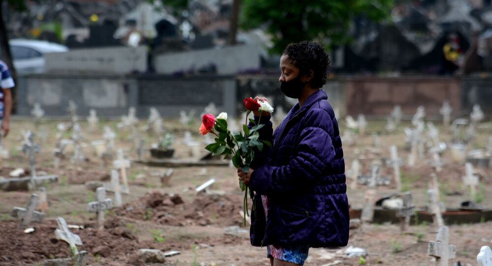 No Rio de Janeiro, uma mulher carrega flores no cemitério São Francisco Xavier no Dia de Finados, em meio à pandemia da COVID-19, em 2 de novembro de 2020