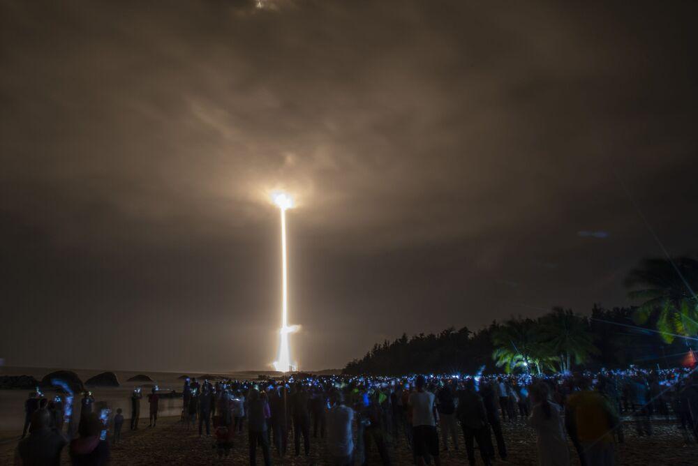 Em praia de Wenchang, multidão observa o foguete portador Long March-5 sendo lançado