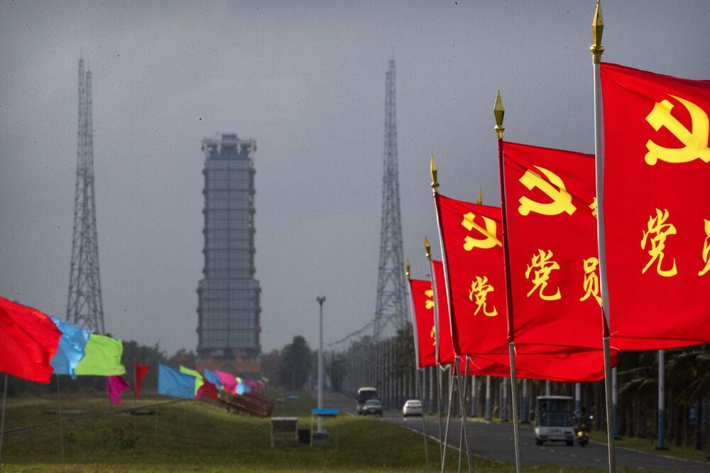 Bandeiras com o símbolo do Partido Comunista da China próximas à área de lançamento do foguete Long March-5