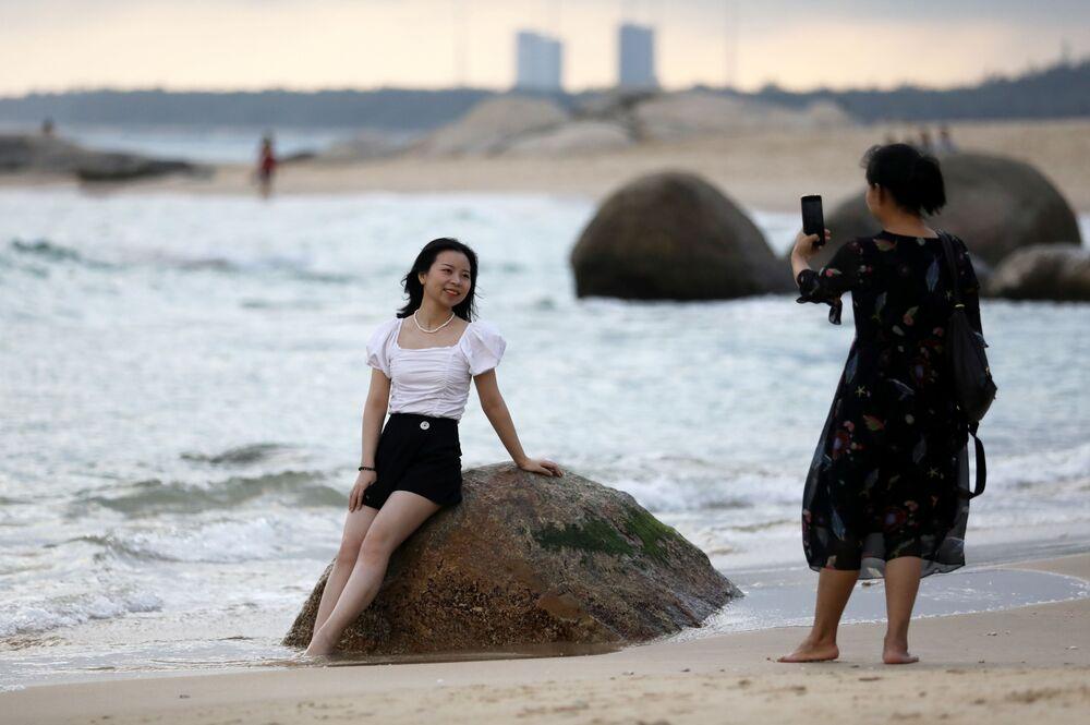 Mulher posa para foto em praia diante do Centro de Lançamento Espacial de Wenchang, no sul da China