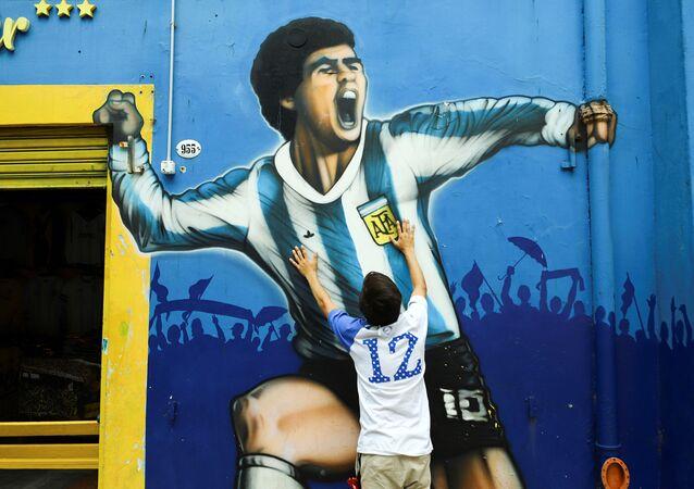 Fã lamenta a morte de Diego Maradona ao lado do seu retrato, na Argentina.
