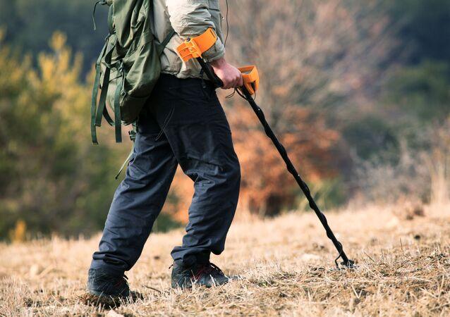 Caçador de tesouros com detector de metal em uma floresta