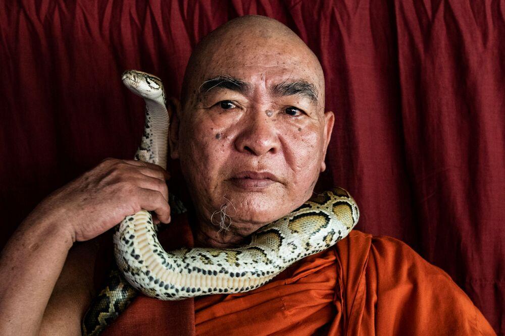 Monge budista Wilatha posando com o píton birmanês resgatado em seu mosteiro que se tornou o santuário de cobras nos arredores de Yangon, Mianmar, 26 de novembro, 2020