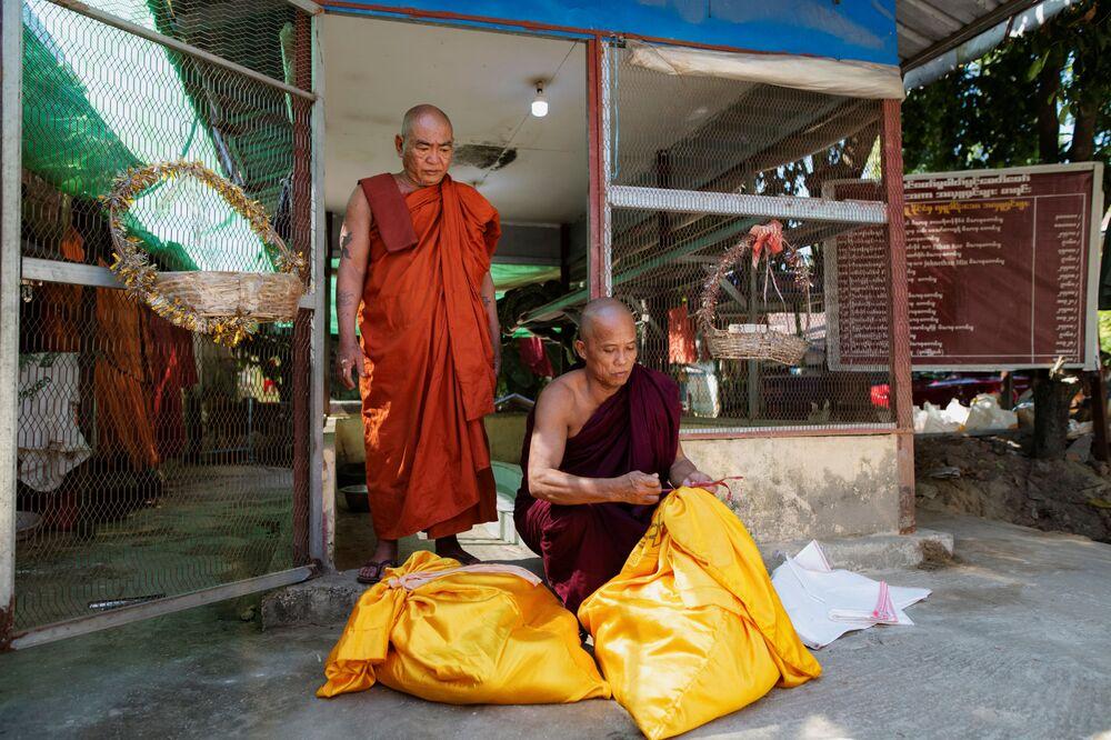 O monge budista no mosteiro que se tornou o santuário de cobras se prepara para soltar os pítons birmaneses em uma floresta nos arredores de Yangon, Mianmar