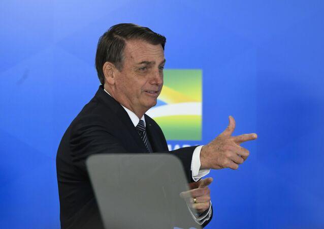 Presidente Jair Bolsonaro faz gesto de arma durante cerimônia no Palácio do Planalto