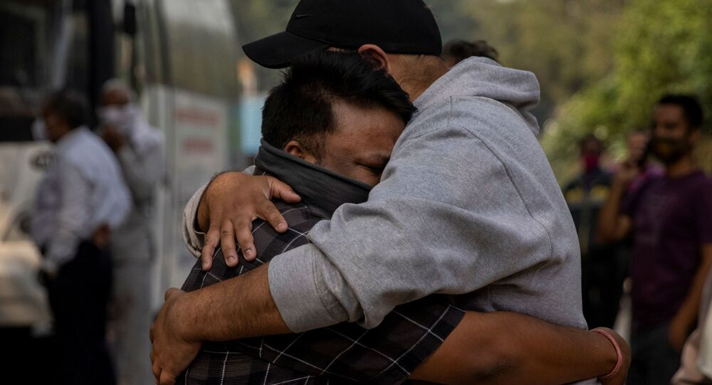 Dois homens choram a morte de parente, vítima da COVID-19, antes da cremação em Nova Deli, Índia.