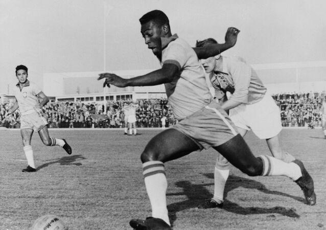 O atacante Pelé dribla zagueiro durante amistoso entre Malmo e o Brasil em 8 de maio de 1960, em Malmo. Pelé marcou dois gols e o Brasil ganhou por 7 a 1