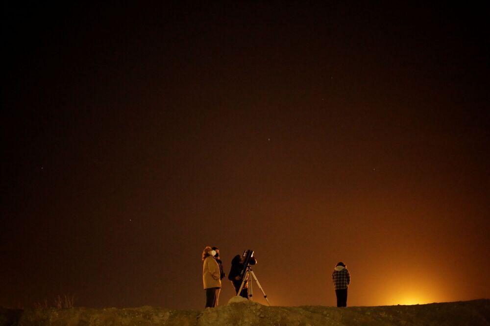 Família usa telescópio para ver a conjunção entre Saturno e Júpiter na fronteira entre o México e os EUA, 21 de dezembro de 2020