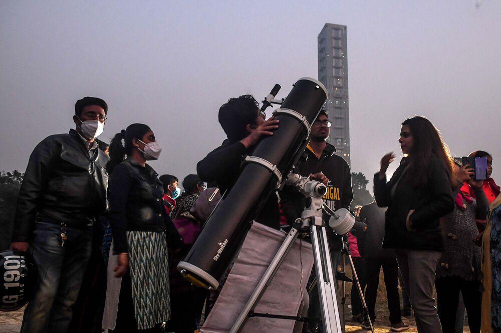 Pessoas ficam em fila para observar o fenômeno raro – grande conjunção entre Saturno e Júpiter em Calcutá, Índia, 21 de dezembro de 2020