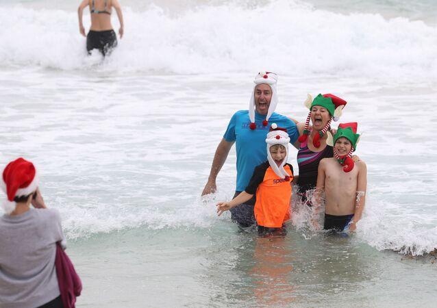 Vestindo gorros natalinos, banhistas marcaram presença na praia Bondi de Sydney, na Austrália, 25 de dezembro de 2020
