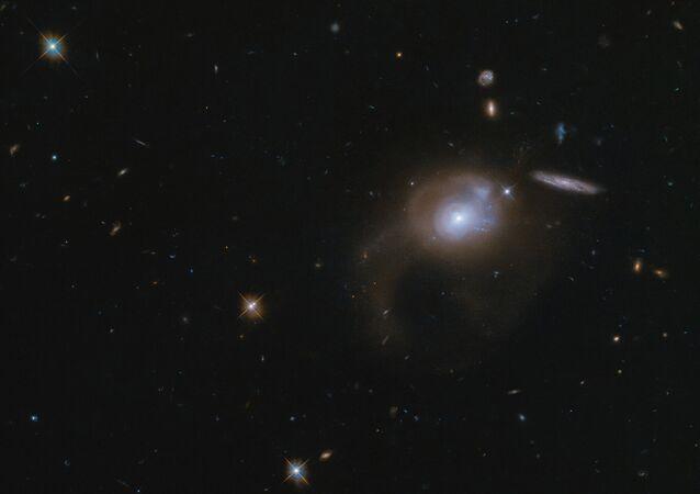 Esta grande extensão de espaço capturada com o Telescópio Espacial Hubble mostra a galáxia SDSSJ225506.80+005839.9. Ao contrário de muitas outras galáxias extravagantes e nebulosas deslumbrantes capturadas pelo Hubble, esta galáxia não tem um nome popular curto, e só é conhecida por suas coordenadas no céu.