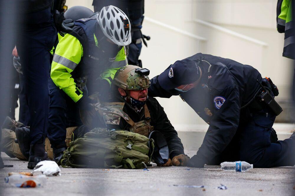 Apoiador do presidente dos EUA, Donald Trump, é detido pela polícia no Capitólio durante o protesto contra a certificação dos resultados das eleições presidenciais de 2020 nos Estados Unidos pelo Congresso, Washington, EUA, 6 de janeiro de 2021