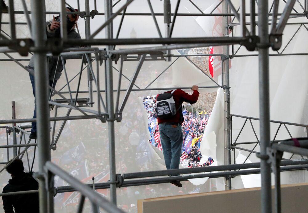 Apoiadores de Donald Trump escalam por andaimes, tentando invadir o Capitólio dos Estados Unidos durante o protesto contra a certificação dos resultados das eleições presidenciais de 2020 pelo Congresso, em Washington, Estados Unidos, 6 de janeiro de 2021