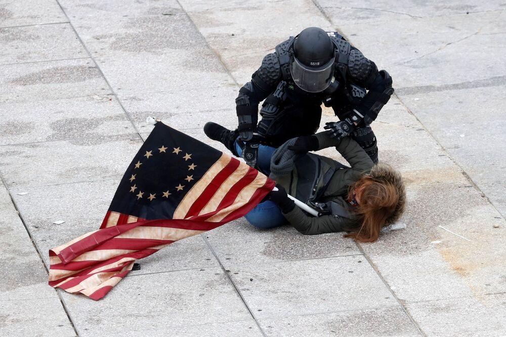 Policial detém uma manifestante pró-Trump durante o protesto contra a certificação dos resultados das eleições presidenciais de 2020 pelo Congresso dos Estados Unidos, em Washington, Estados Unidos, 6 de janeiro de 2021