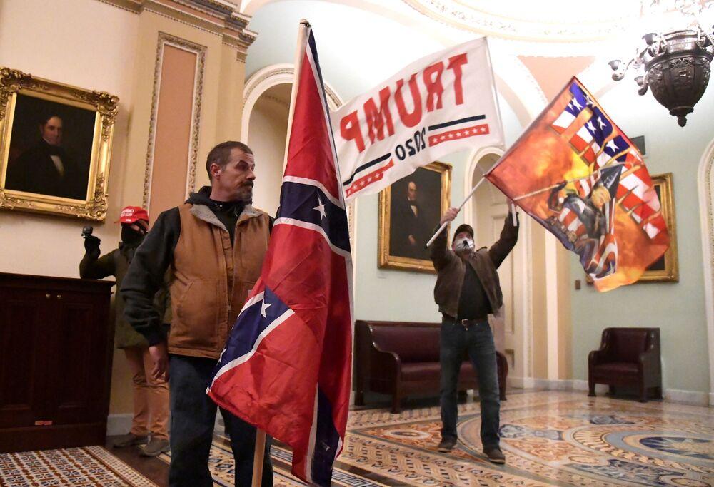 Apoiadores do presidente dos EUA, Donald Trump, protestam no segundo andar do Capitólio dos EUA, perto da entrada para o Senado, depois de quebrar a proteção de segurança, Washington, EUA, 6 de janeiro de 2021