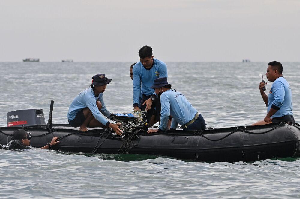 Mergulhadores da Marinha da Indonésia coletam destroços do avião de passageiros durante as operações de busca e salvamento