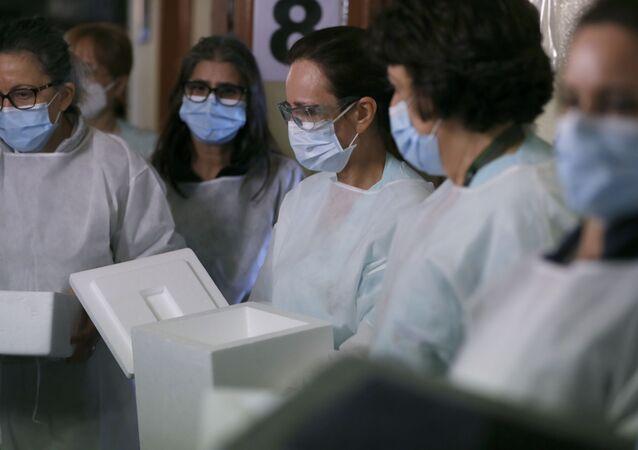 Enfermeiras portuguesas segurando caixas de Styrofoam para recolher doses da vacina da Pfizer/BioNTech contra COVID-19 para serem distribuídas nos hospitais de Lisboa
