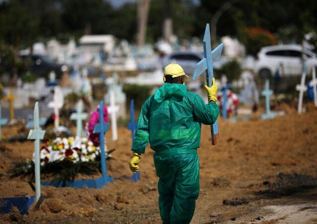 Agente funerário carrega cruz utilizada em túmulos de vítimas da COVID-19 em Manaus, no Amazonas.