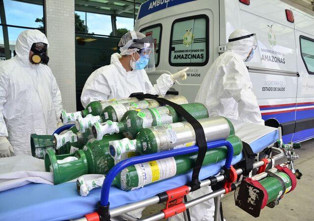 Enfermeiros carregam cilindros de oxigênio em hospital de Manaus (AM). Familiares de internados precisam comprar oxigênio para manter os seus parentes vivos.