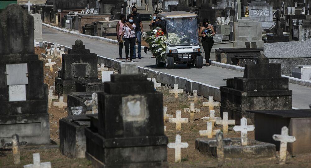 Familiares acompanham enterro de vítima da COVID-19 em cemitério no Rio de Janeiro.