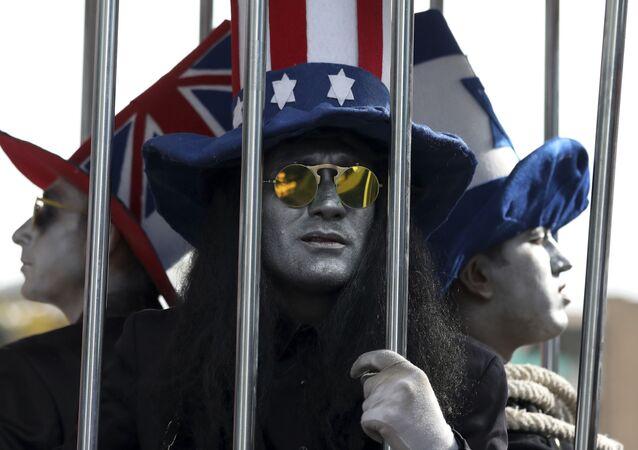 Manifestantes usam chapéus com bandeiras de EUA, Reino Unido e Israel em protesto em frente à antiga Embaixada dos EUA em Teerã, Irã, 4 de novembro de 2019