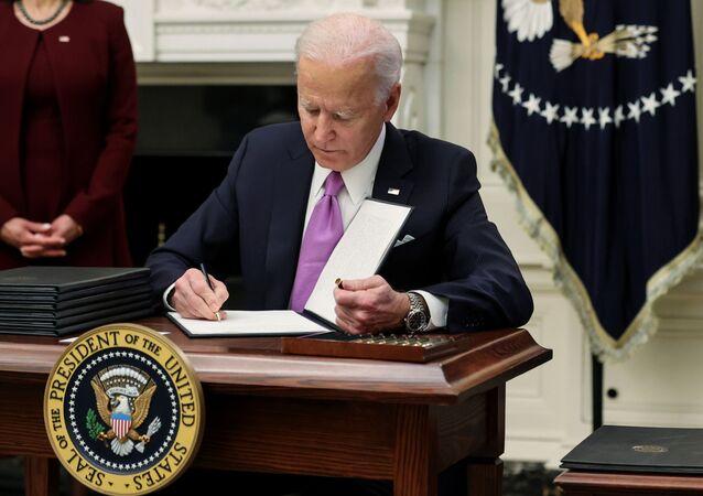 Joe Biden assina ordem executiva durante seu primeiro dia na presidência dos EUA, em Washigton, EUA, 21 de janeiro de 2021