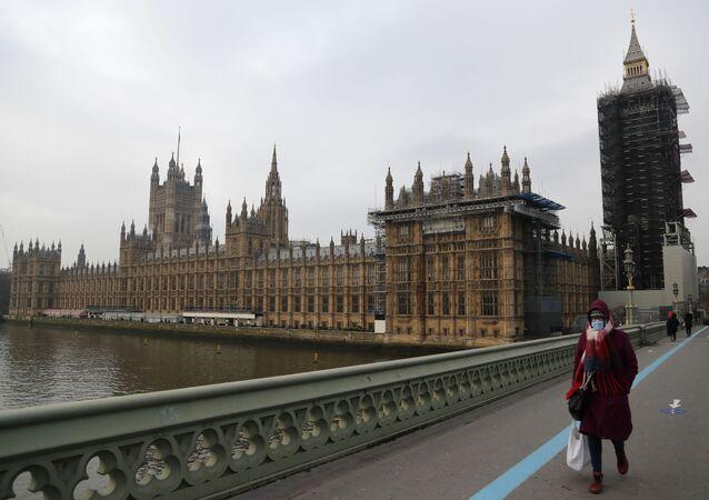 Pedestre passa pela ponte de Westminster, ao lado do Parlamento britânico, Londres, Reino Unido, 8 de janeiro de 2021