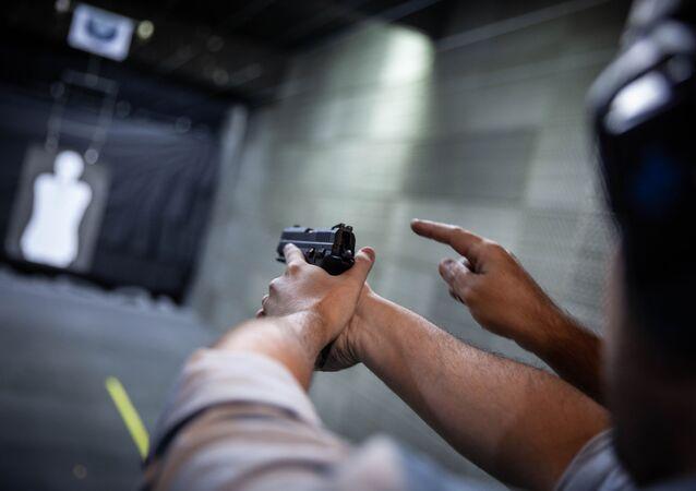 Homem aprende técnica de disparo de arma de fogo.
