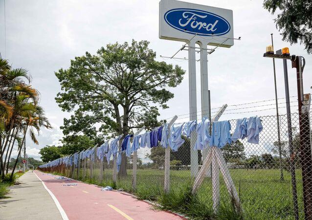 Trabalhadores da Ford em Taubaté realizaram um protesto na portaria principal da fábrica. Eles colocaram uniformes pendurados nas grades da empresa e anotaram em cada camisa o nome das famílias que serão afetadas pelo fechamento da montadora.