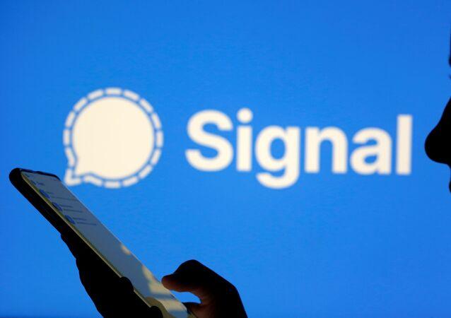 Mulher segura smartphone com o aplicativo de mensagens Signal em fundo, em 13 de janeiro de 2021