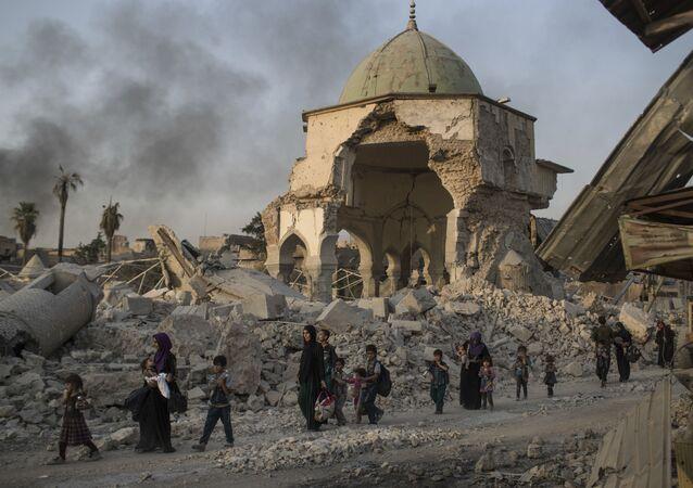 Civis iraquianos deixam a cidade de Mossul, no Iraque, destruída por confrontos entre o Daesh (foto de arquivo)