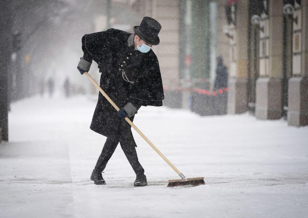 Empregado do Hotel Adlon limpa a calçada da neve em Berlim, Alemanha, em 8 de fevereiro de 2021