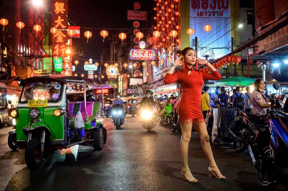 Mulher posa para foto em rua de Bangkok, Tailândia, decorada para celebrar o Ano Novo Lunar, em 9 de fevereiro de 2021
