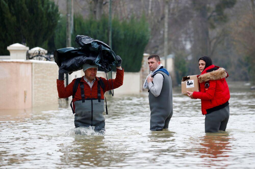 Moradores caminham em ruas inundadas pelo rio Marne após dias de chuva em Esbly, perto de Paris, França, 8 de fevereiro de 2021