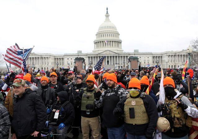 Membros do Proud Boys, grupo de extrema-direita, fazem gestos de mão OK indicando poder branco, em protesto junto do Capitólio em Washington, EUA, 6 de janeiro de 2021