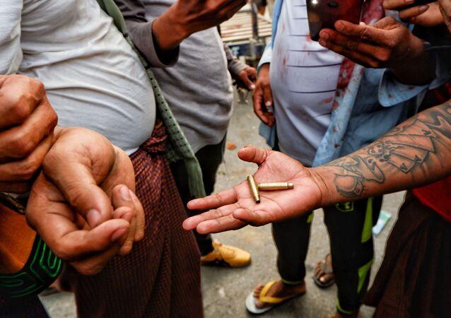 Manifestantes seguram munição letal usada por forças de segurança durante protesto em Mianmar.