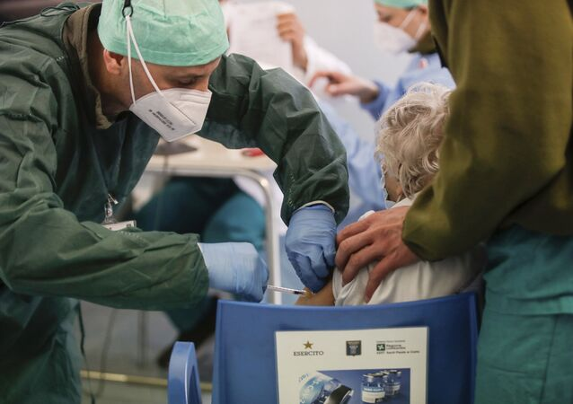 Em Milão, na Itália, um profissional de saúde aplica uma dose de uma vacina contra a COVID-19 em uma idosa, em 18 de fevereiro de 2021
