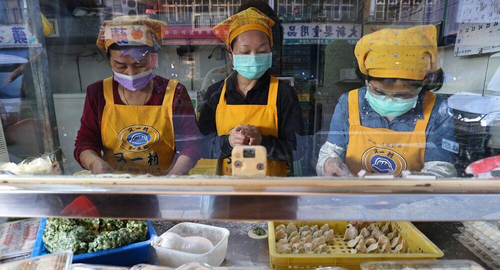 Mulheres usam máscaras para evitar a disseminação da COVID-19 em mercado de Taipé, capital de Taiwan.