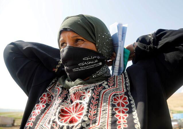 Mulher se registra para participar das próximas eleições em territórios palestinos, na Cisjordânia ocupada, 16 de fevereiro de 2021