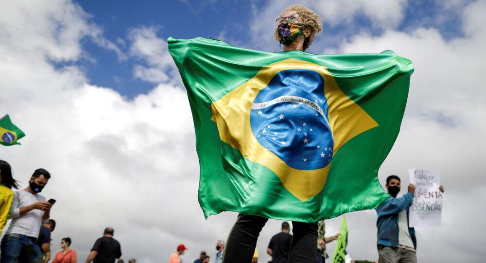 Mulher segura bandeira do Brasil em protesto contra medidas de combate à COVID-19, em Brasília, 1º de março de 2021