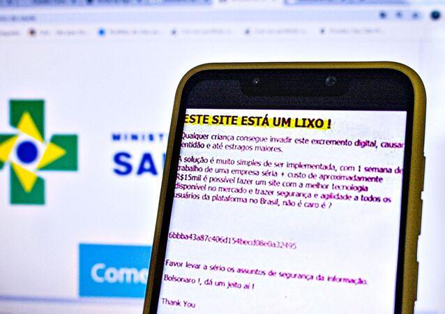 Um smartphone mostra uma mensagem deixada por um hacker em ataque ao site do Ministério da Saúde, mostrado no fundo.