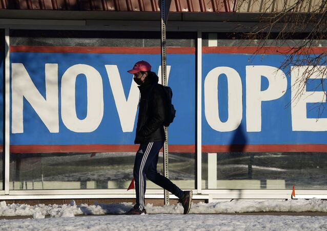 Em Boulder, nos Estados Unidos, um pedestre caminha vestindo uma máscara de proteção contra a COVID-19 em frente a uma placa de um restaurante dizendo estamos abertos, em 25 de fevereiro de 2021