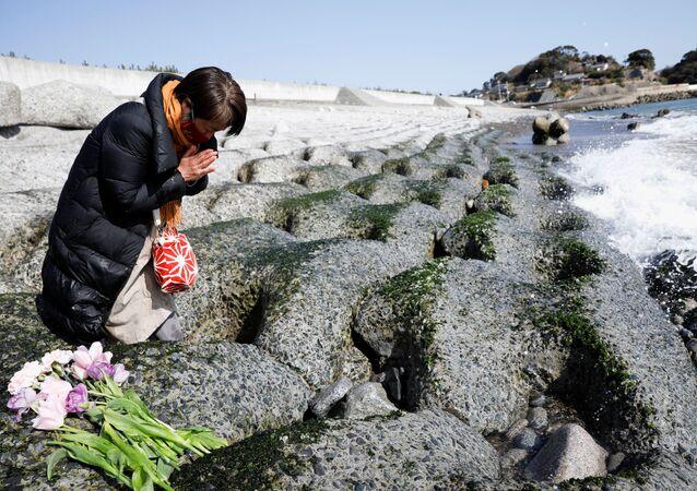 Mulher reza pelas vítimas do terremoto de 2011, em Iwaki, prefeitura de Fukushima, Japão, 11 de março de 2021