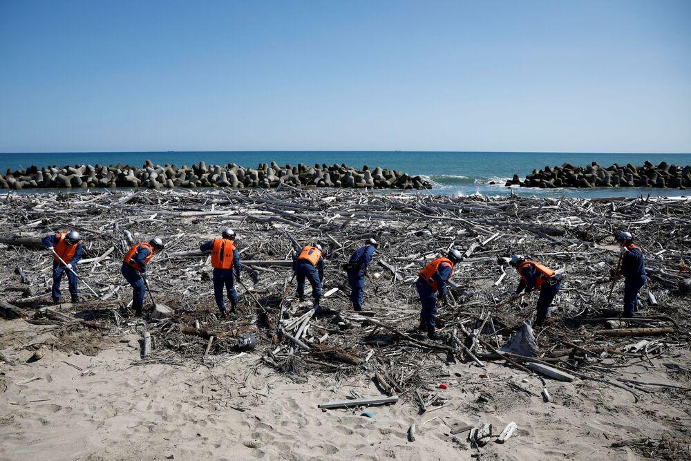 Bombeiros procuram desaparecidos após o terremoto de 2011, em Namie, prefeitura de Fukushima, Japão