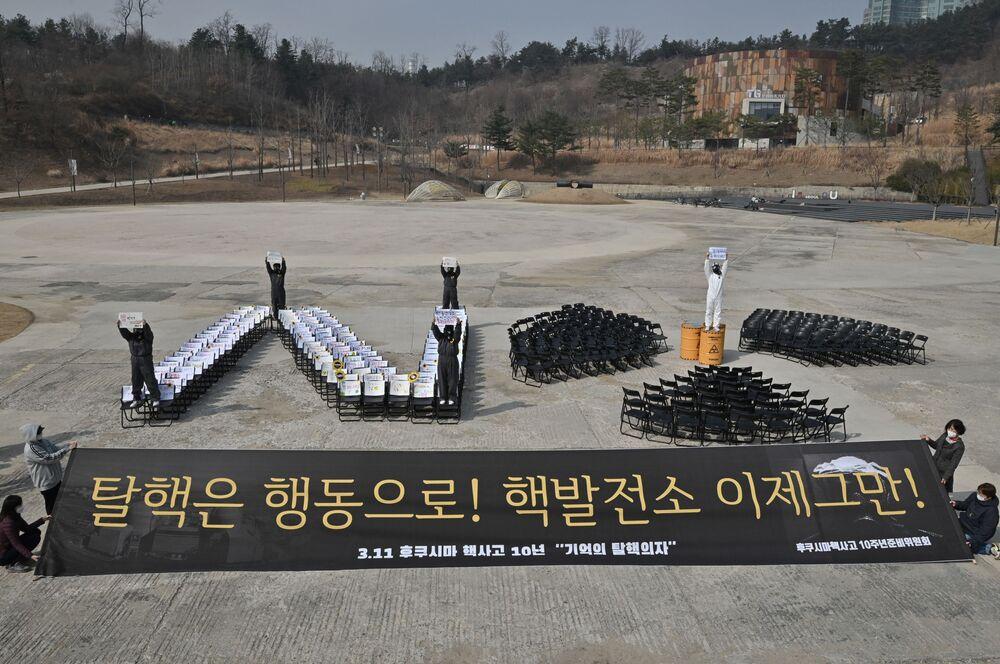 Ambientalistas sul-coreanos segurando um grande cartaz que diz Não mais usinas nucleares! durante um protesto antinuclear para marcar o 10º aniversário do desastre de Fukushima, Seul, 11 de março de 2021