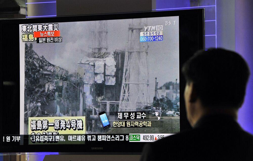 Passageiros sul-coreanos passam por noticiários sobre a explosão e colapso na usina nuclear japonesa de Fukushima Daiichi na estação ferroviária em Seul, 16 de março de 2011