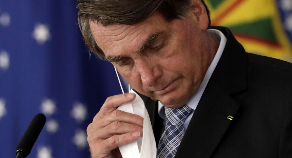 Presidente do Brasil, Jair Bolsonaro, retira máscara protetora durante cerimônia no Palácio do Planalto, 10 de março de 2021